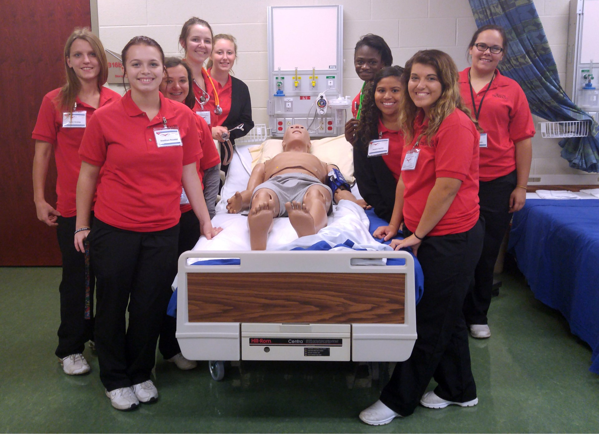 Female Health Technology students in red shirts surround hospital bed with human simulator HAL
