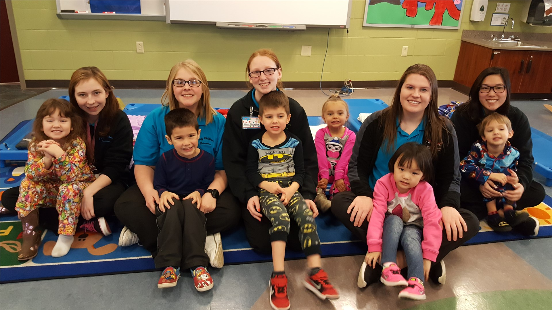 Female Early Childhood Education students sitting on the floor with preschoolers