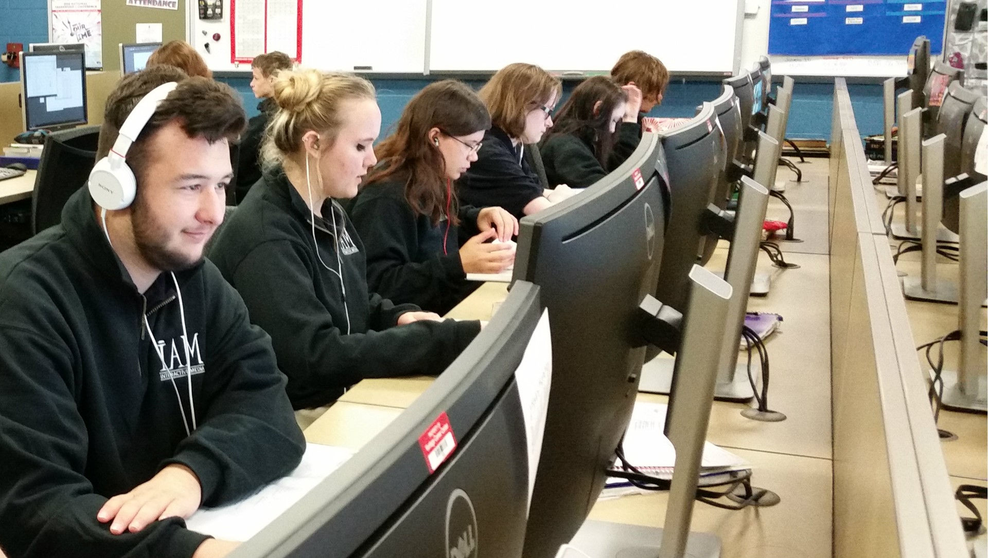 Male and female Interactive Media students sitting in a row at computers