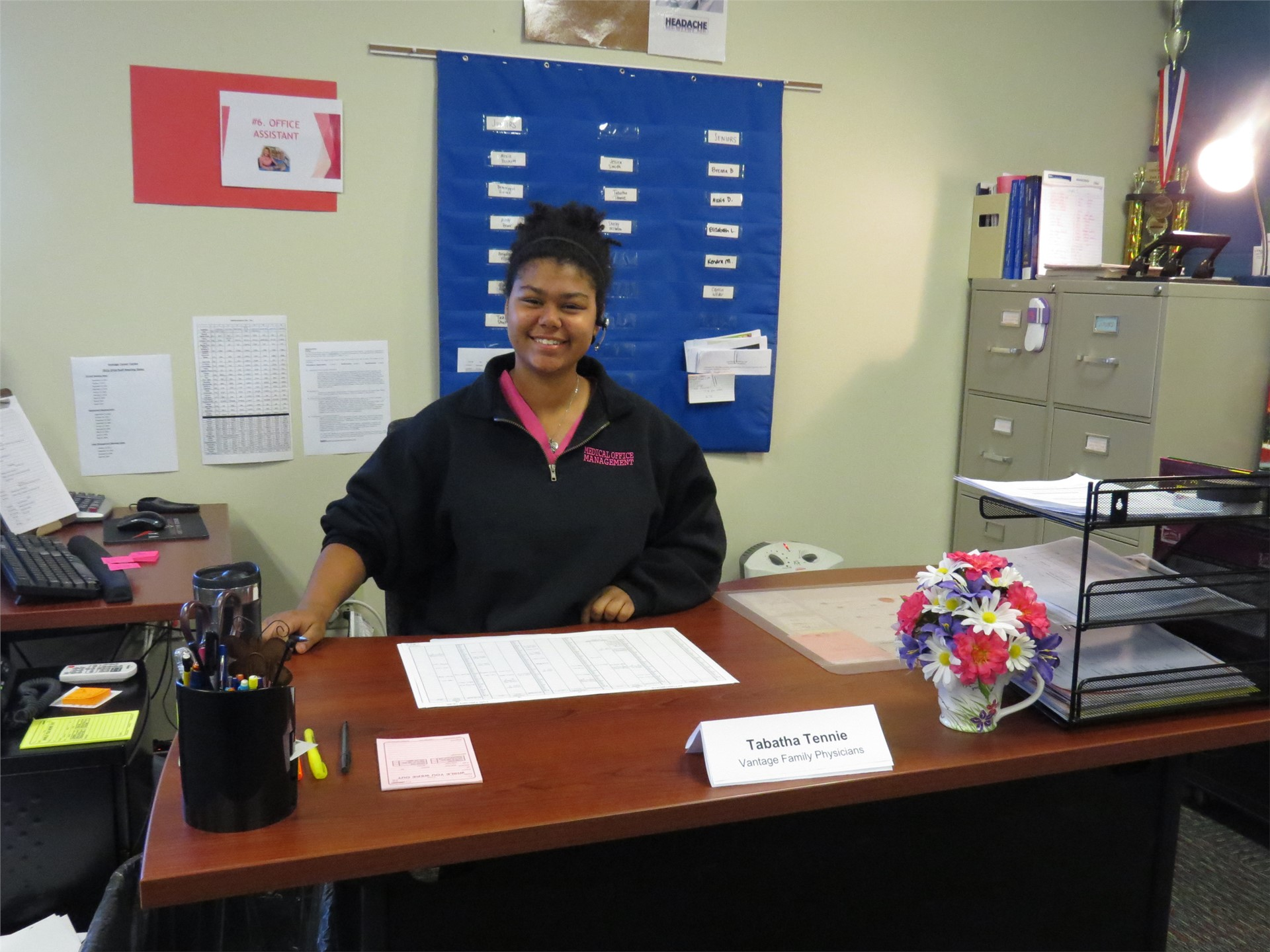 Female Medical Office Management student smiling, sitting at desk