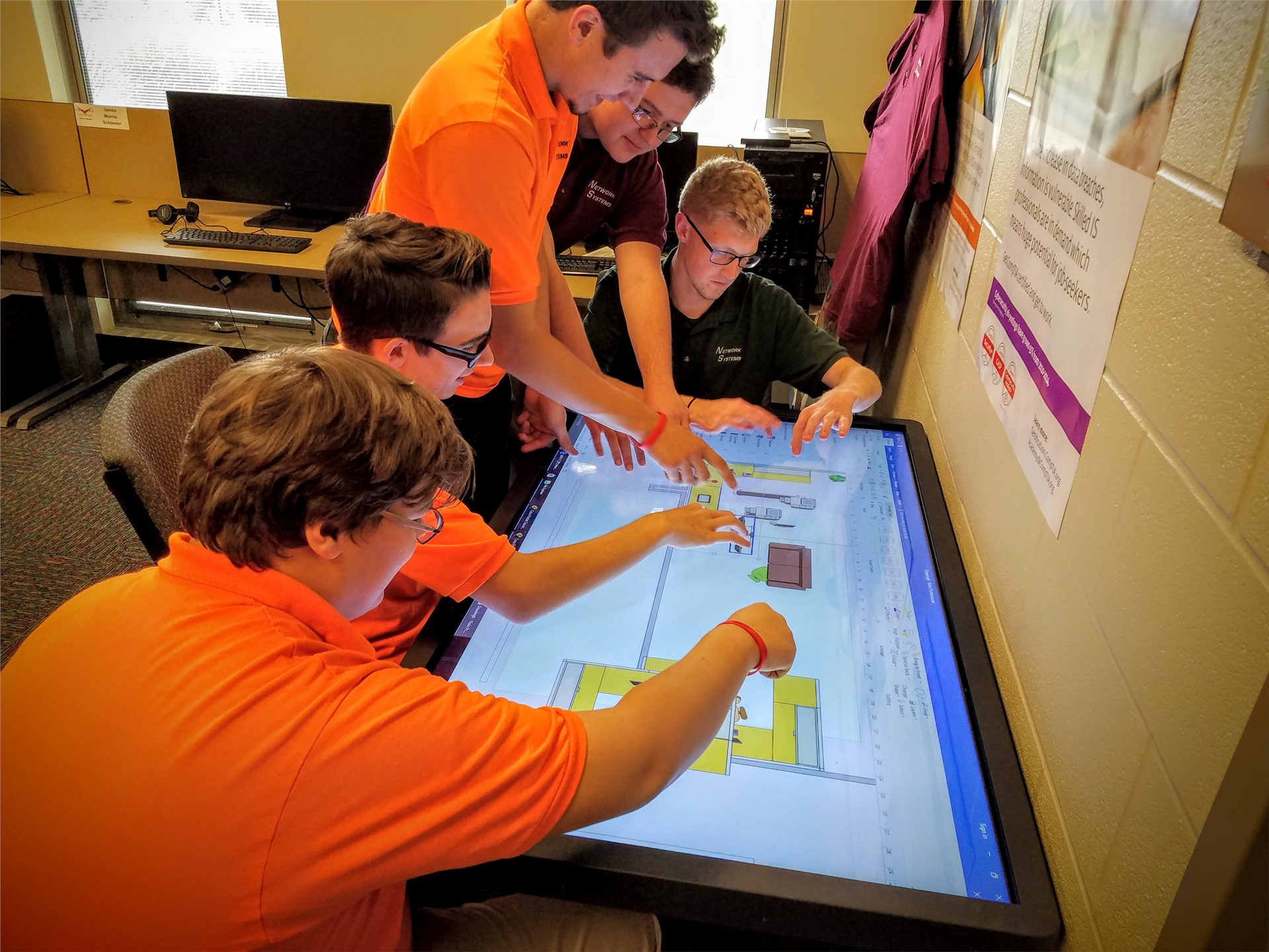5 male Network Systems students working on a large table top monitor