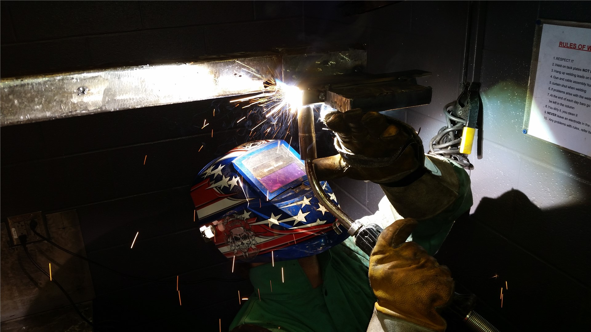 Welder with stars and stripes welding helmet on