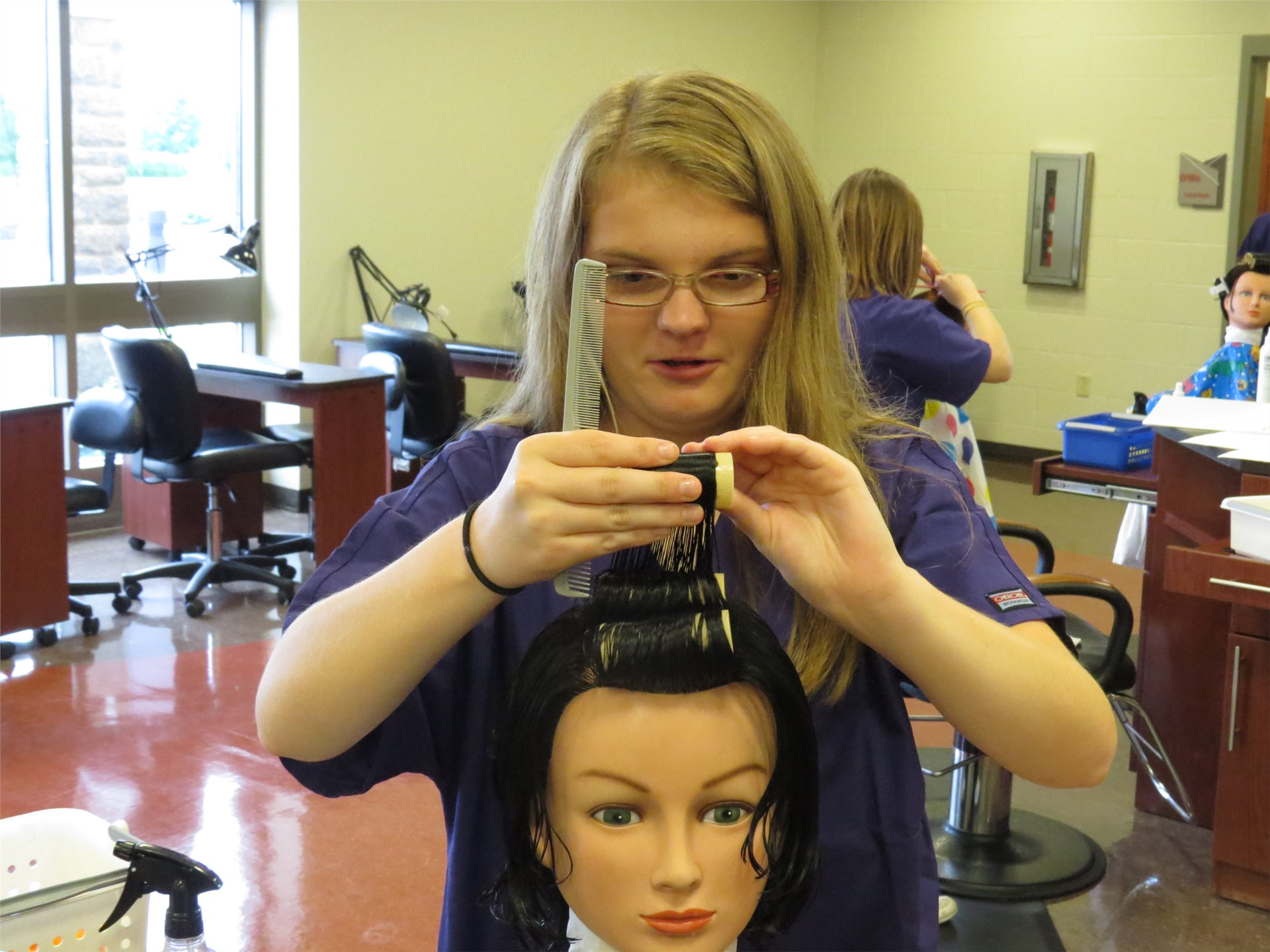 A female Cosmetology student putting curlers on a mannequin