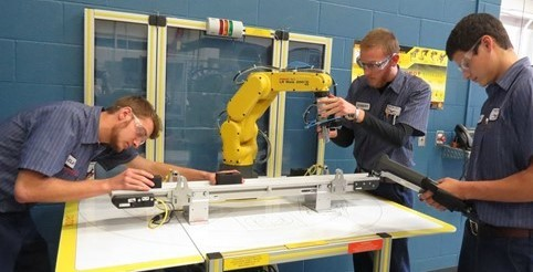 3 male Industrial Mechanics students working on robotic arm