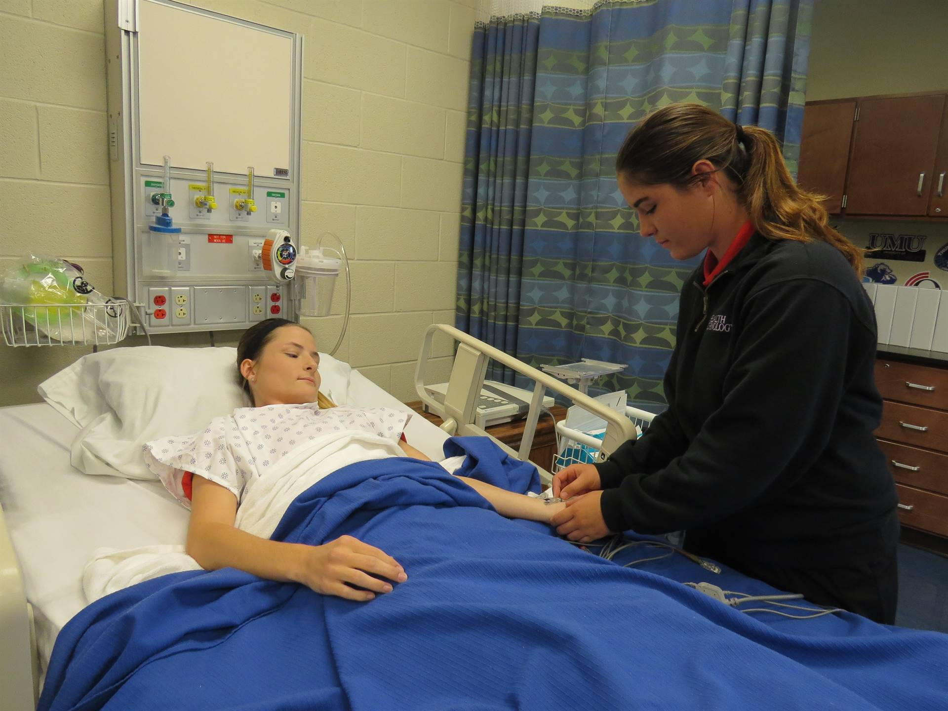 Female patient in hospital bed with female student attending to her