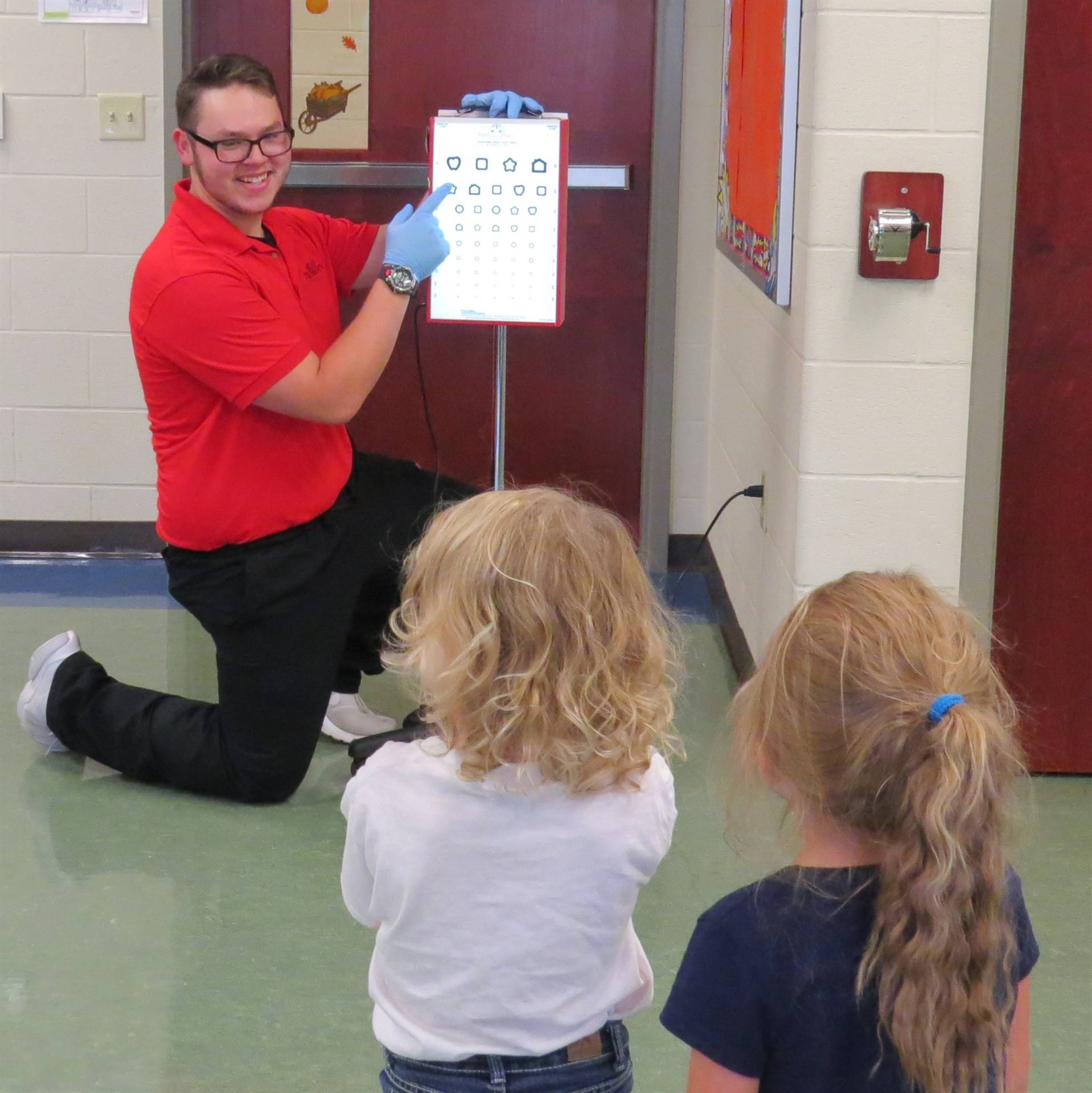 Smiling male Health Tech student giving eye test to 2 female preschoolers