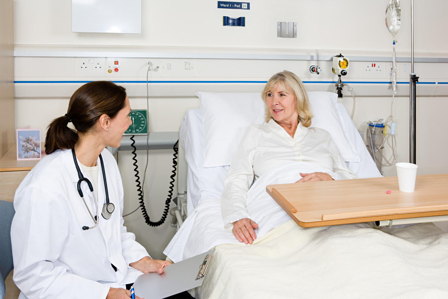 nursing student evaluating female patient at bedside
