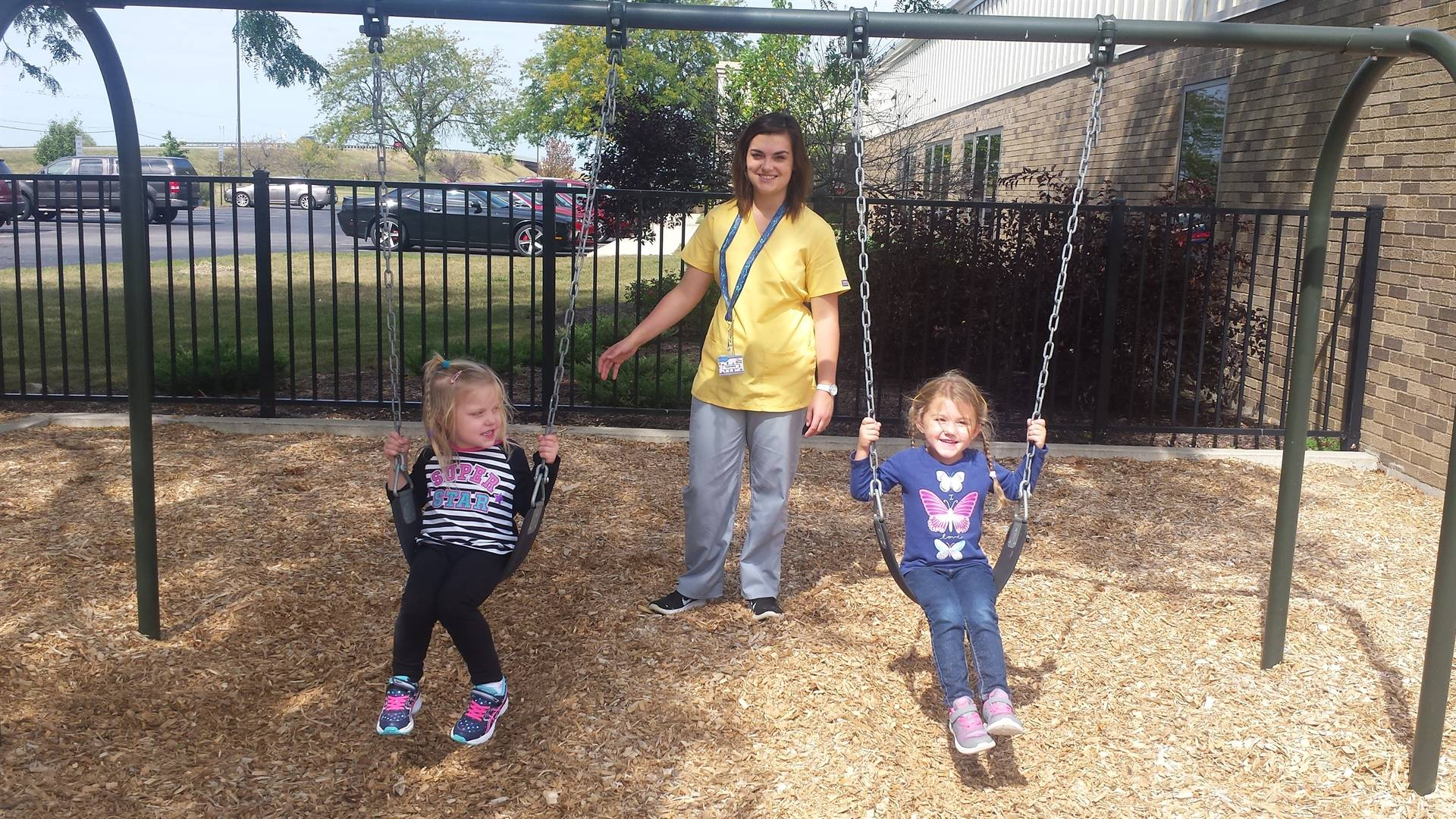 preschoolers with early childhood student outside on swings