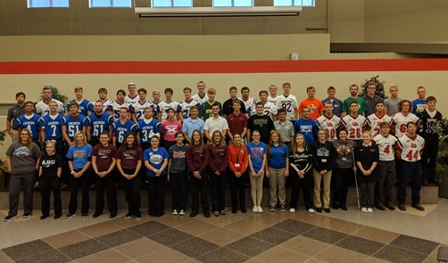 60 male and female student athletes stand together on stage for Fall Sports Spirit Day.