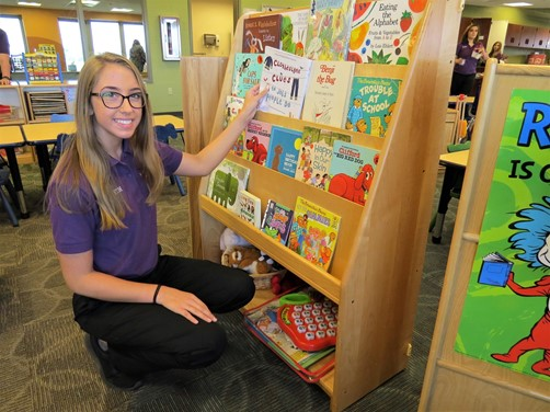 Early Childhood student organizing a book shelf while preparing for incoming preschool students