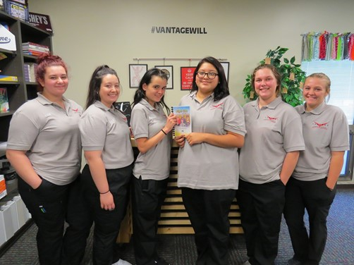 Medical Office Management students holding a cookbook they assisted in creating.