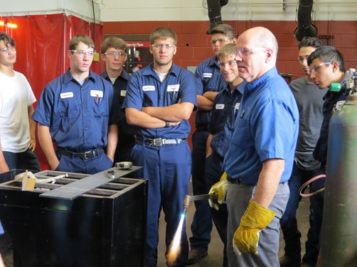 Welding students gather around the Welding Instructor to learn how to properly handle a welding torch.