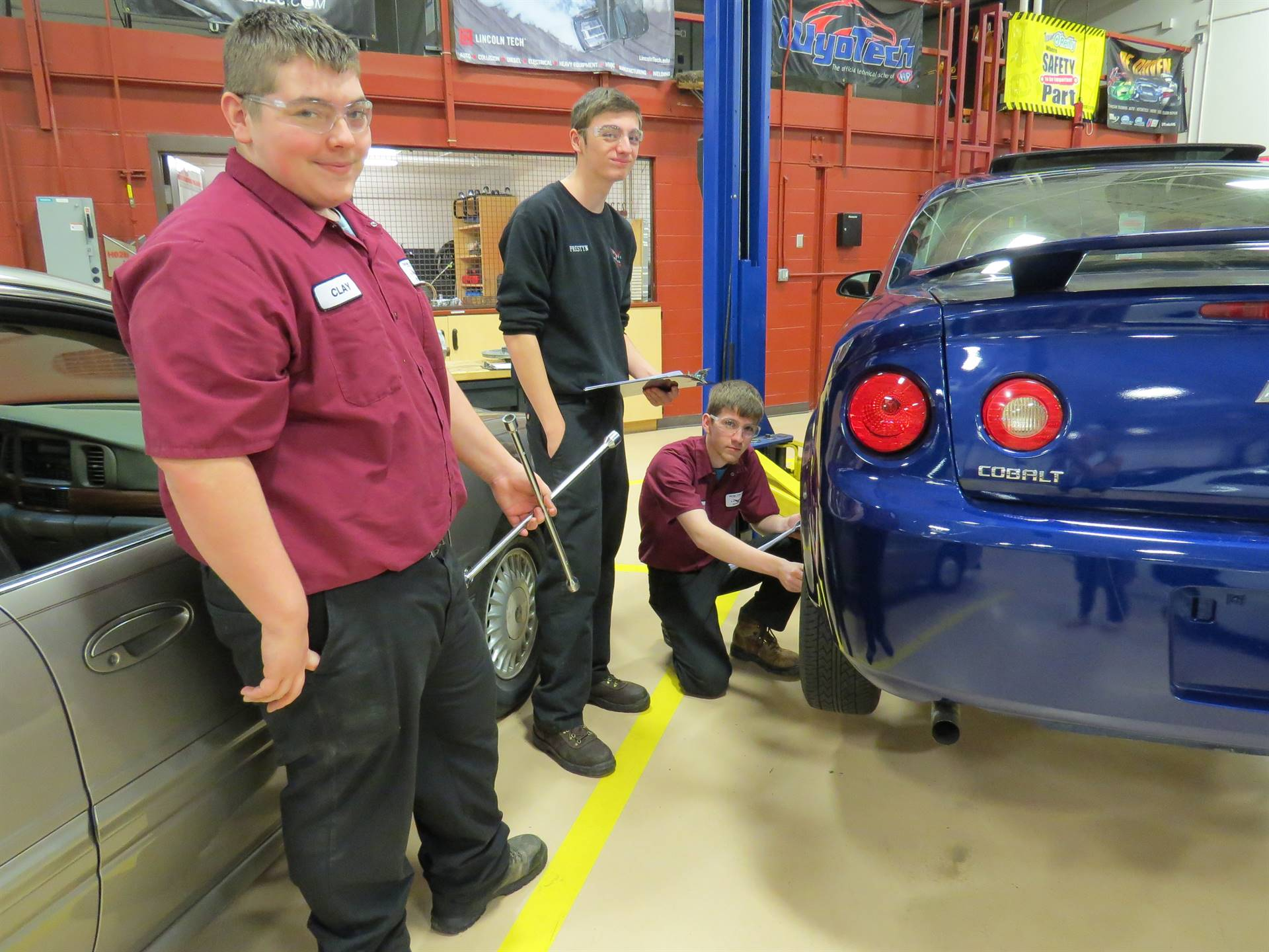 Auto Technology students work together to change a tire.