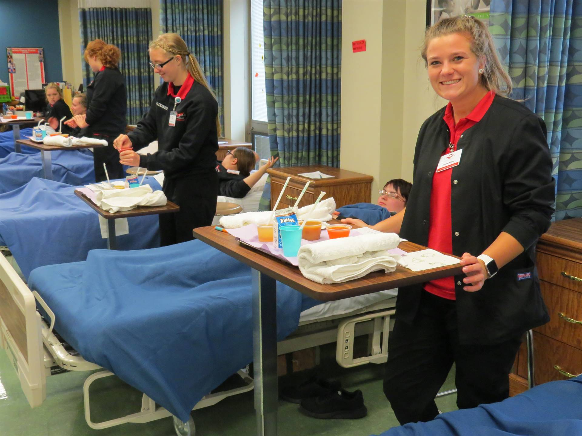 Health Technology students prepare to feed a resident.