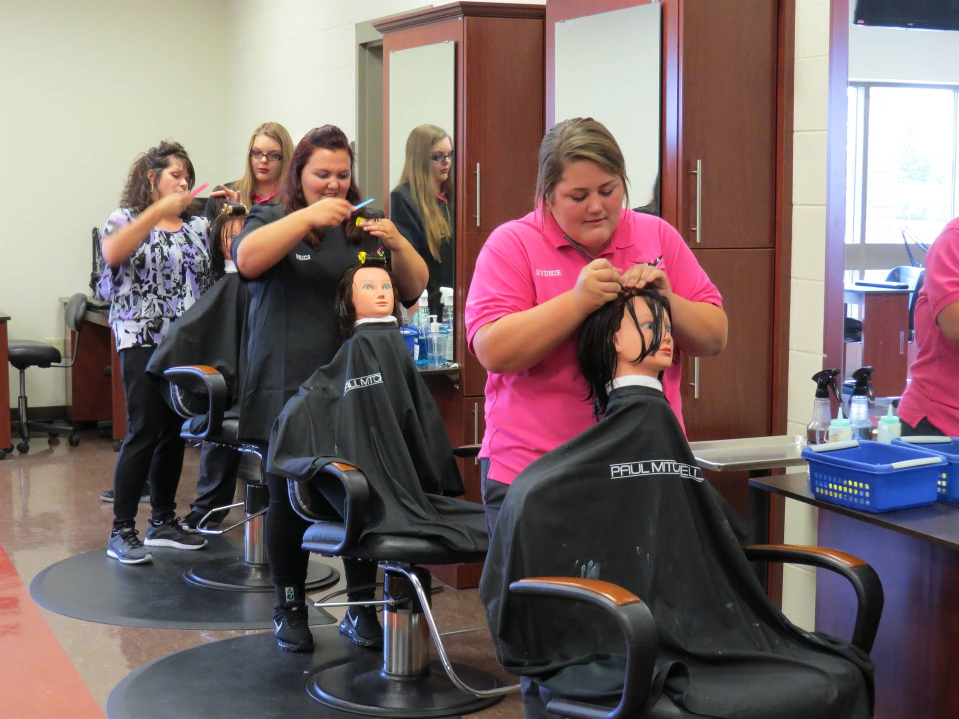 Cosmetology students practice beauty service skills on mannequins.
