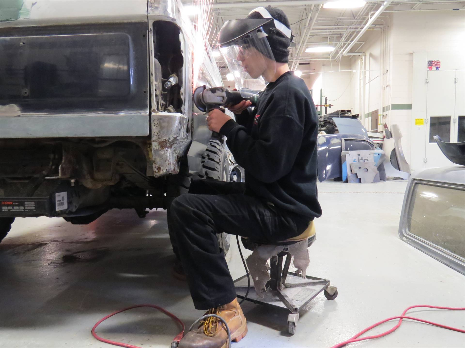Auto Body Repair student is using a grinding tool to smooth the surface of a vehicle.