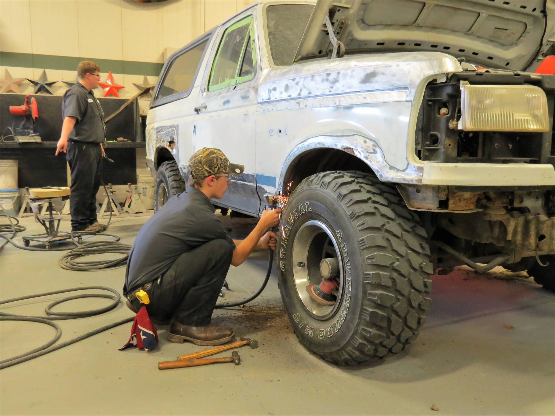 Auto Body Repair students uses a grinding tool to smooth the surface on a customer vehicle.