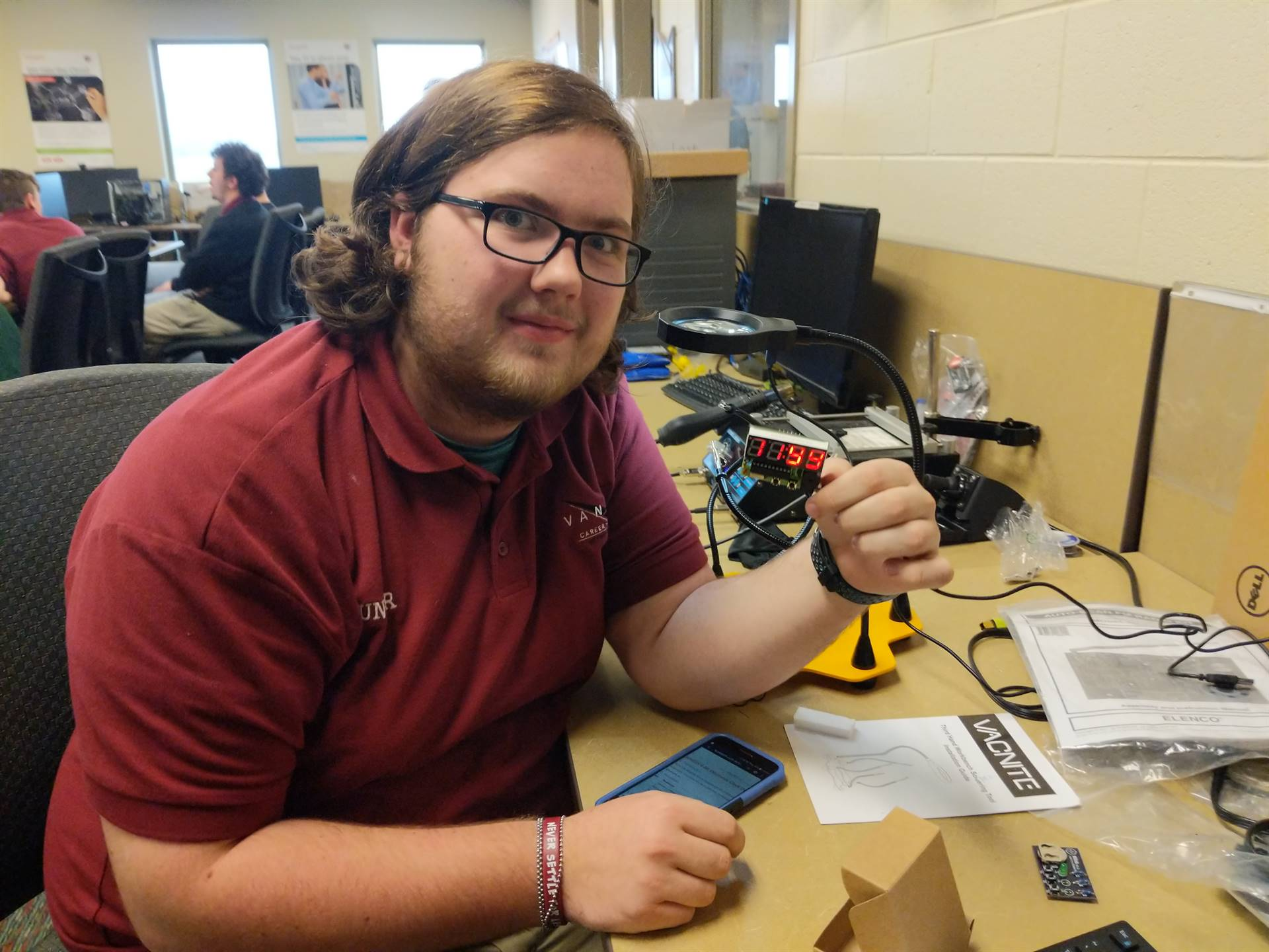 Network systems student uses a soldering tool on an alarm clock.