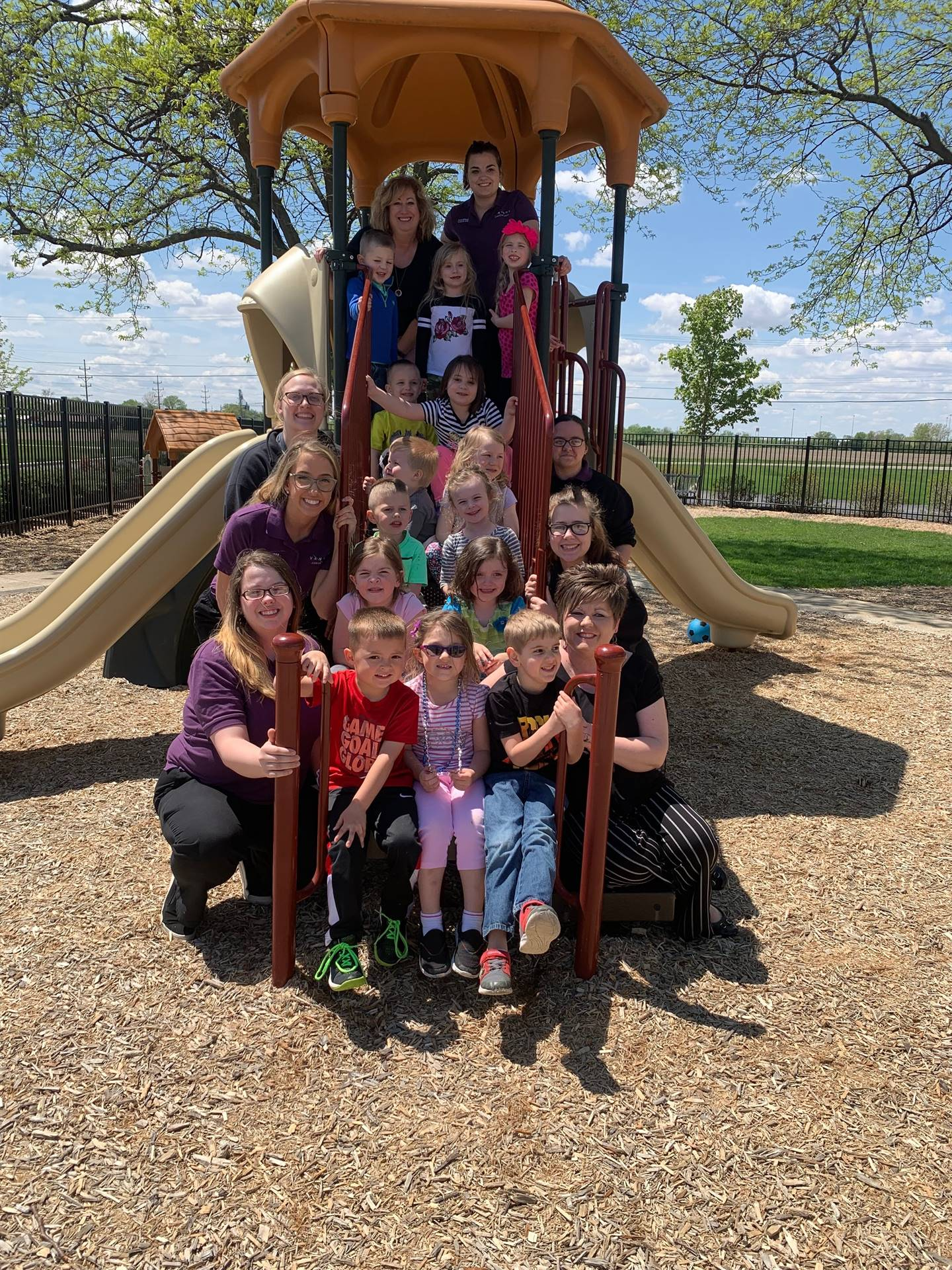 Early Childhood Education students pose with the preschool students on the playground equipment.